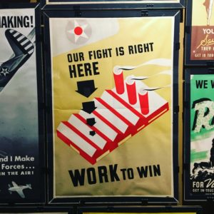 "Photo of a poster with a factory reading ""Our fight is right HERE WORK to win"""