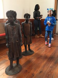 Bronze sculptures of enslaved children with one actual child in a church at the Whitney Plantation