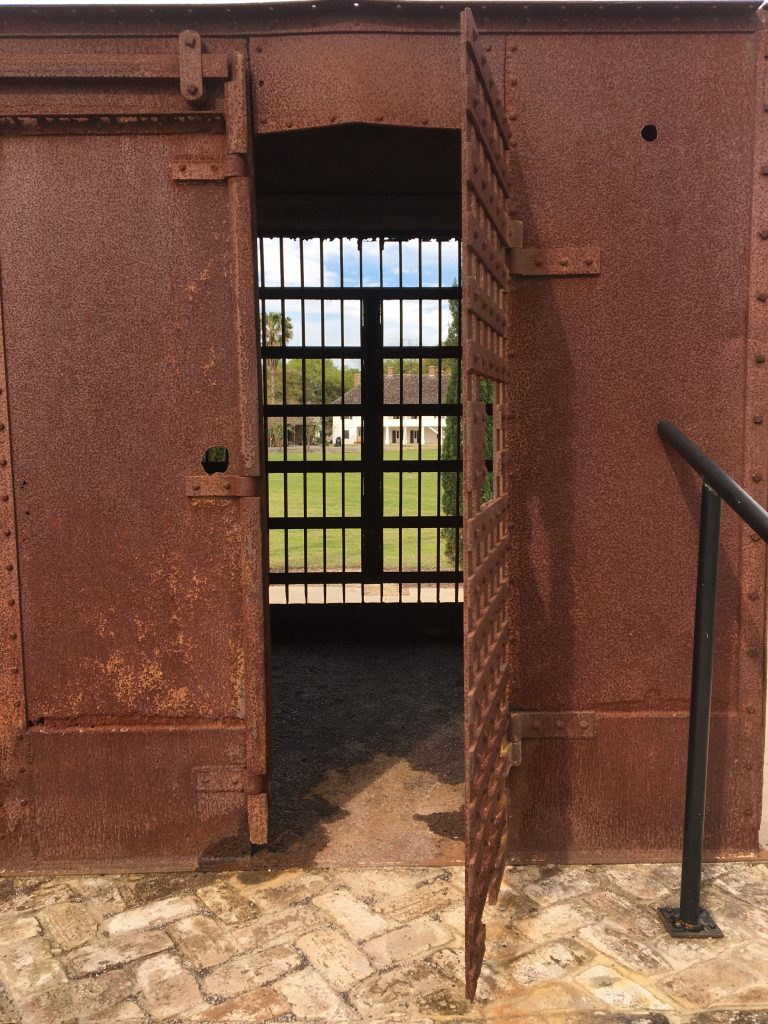 View of the manor house through the open door and bars of an iron prison box